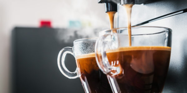 freshly brewed coffee is poured from the coffee machine into glass cups in the kitchen at home